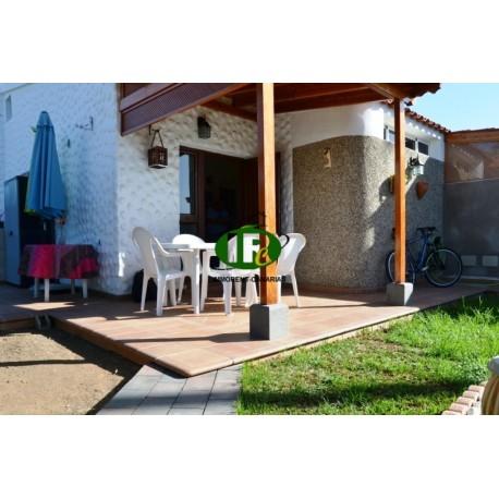 Amplio bungalow de 2 dormitorios y una gran terraza, vallado. Parcialmente embaldosado y cubierto