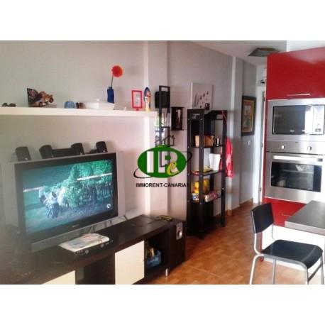 Apartment mit 1 Schlafzimmer. Wohnbereich mit Sofa, großem TV und internationalen Programmen
